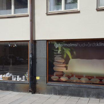 Fönsterdekor samt smidesskylt Östermalmshudvårdsklinik